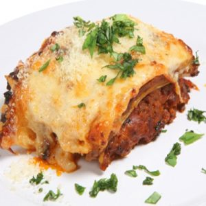 Baked lasagne verdi garnished with fresh basil leaves on a white plate